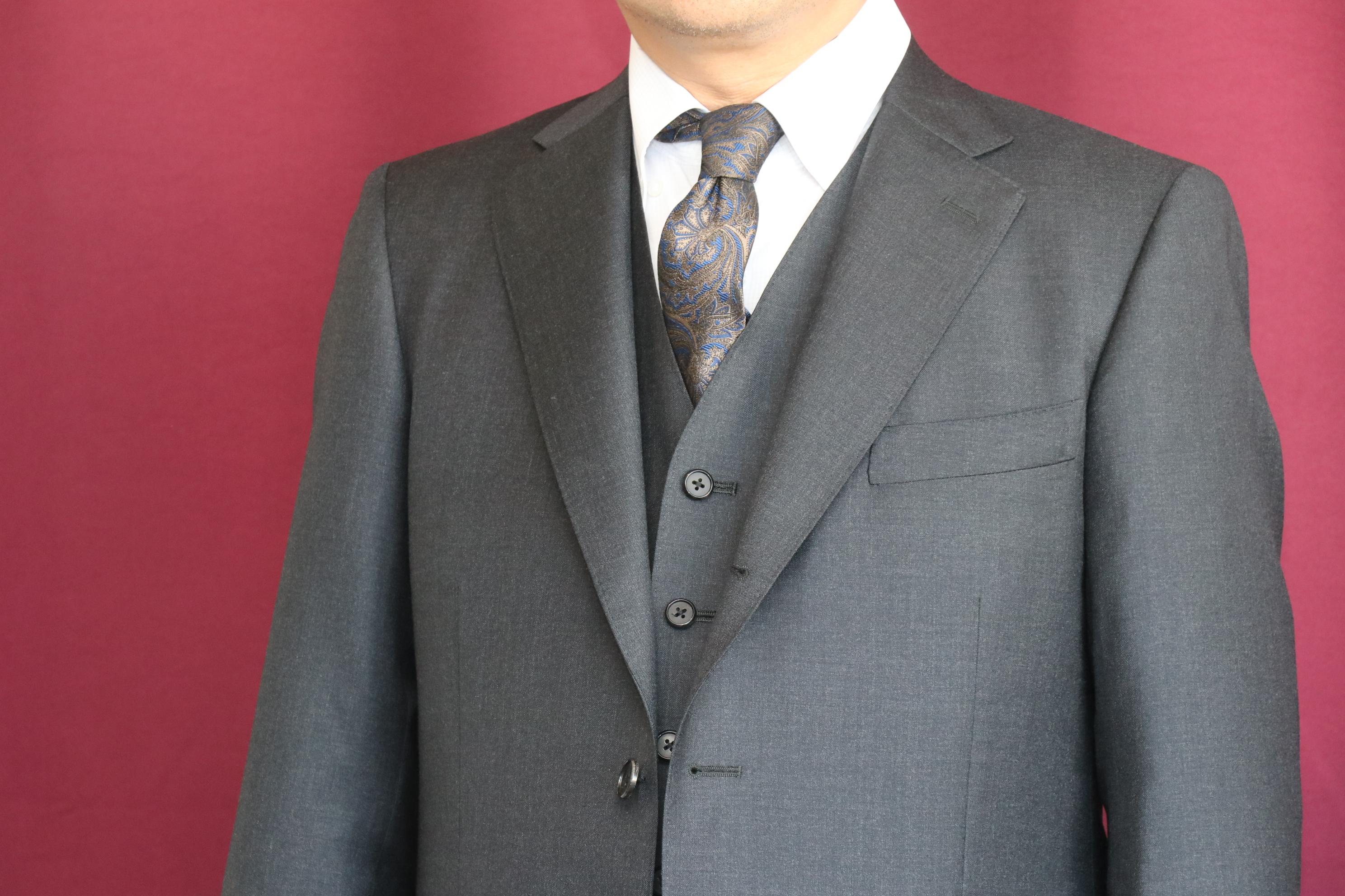 光沢感あるチャコールグレーのスリーピース にクラシックなペイズリーのネクタイを合わせる